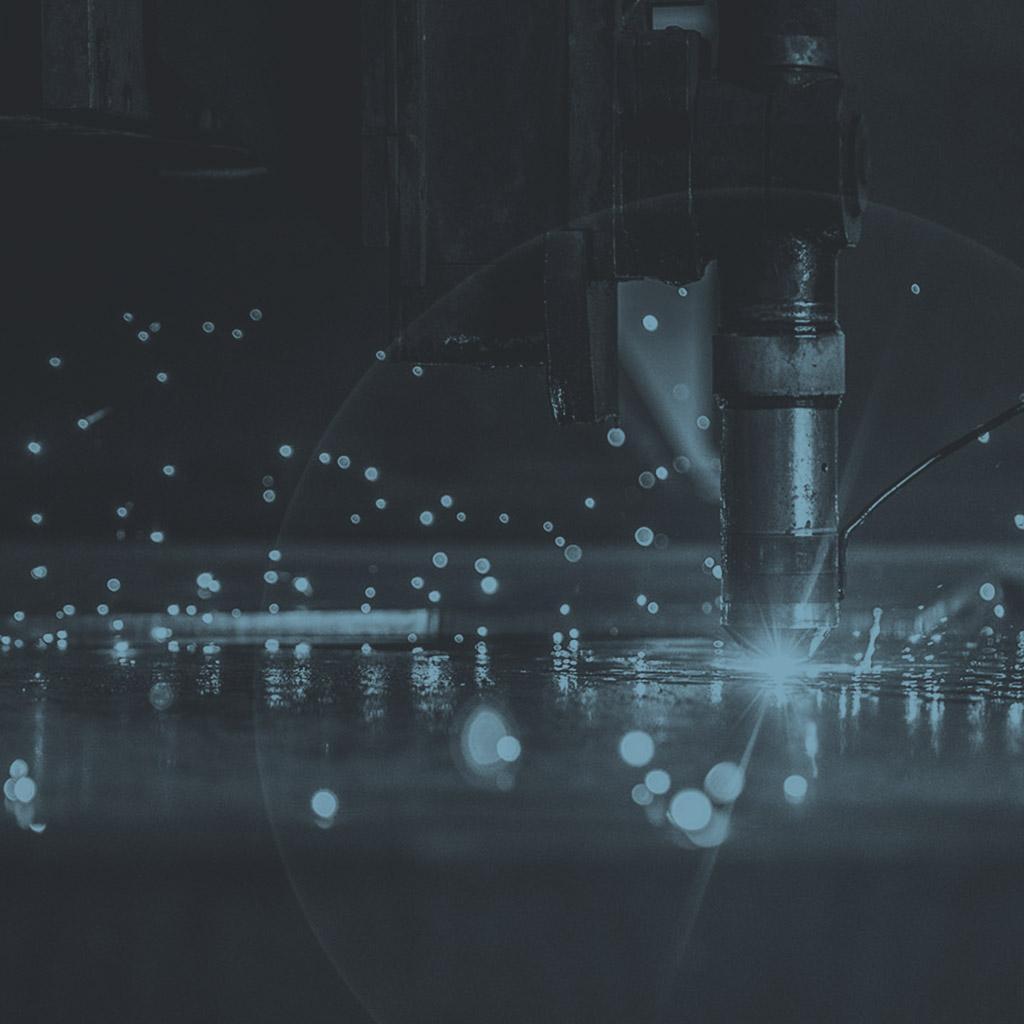 Grafika przedstawiająca laser CNC w trakcie wycinania w arkuszu metalu.